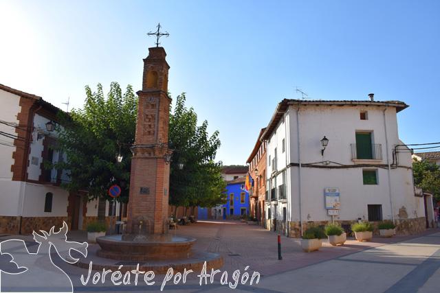Peirón de San Antón en primer término, en la plaza mayor de Jaraba.